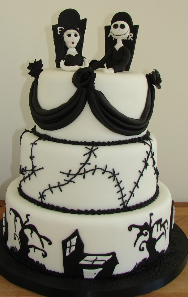 a black and white wedding cake with a scar tier, a scary tree tier, sugar curtains, skeleton toppers with gravestones is a stylish idea for a Halloween wedding