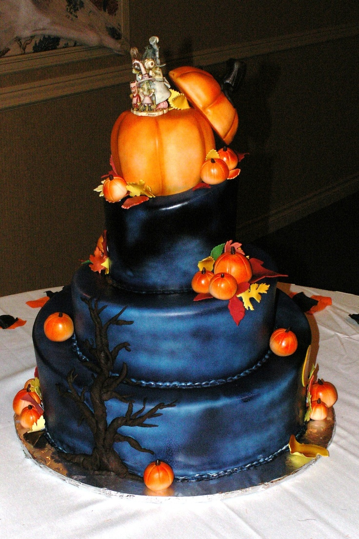a black navy wedding cake with a scary tree, faux pumpkins, faux leaves and a large pumpkin with quirky toppers for a Halloween wedding