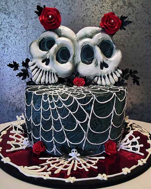 a black and white spiderweb wedding cake with red blooms and large skull toppers plus black leaves