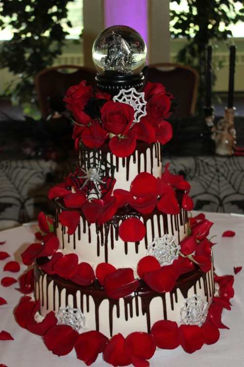 a white wedding cake with chocolate drip, red petals, red roses, spiders, spiderwebs, a dragon ball on top for a Halloween wedding