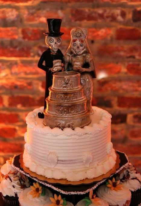 a white buttercream wedding cake with unique skeleton toppers cutting a cake is a very unusual and bold idea