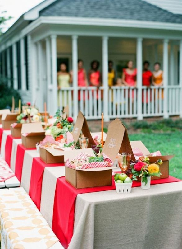 a bright rustic picnic with red and white textiles, bright blooms and apples and boxes with food