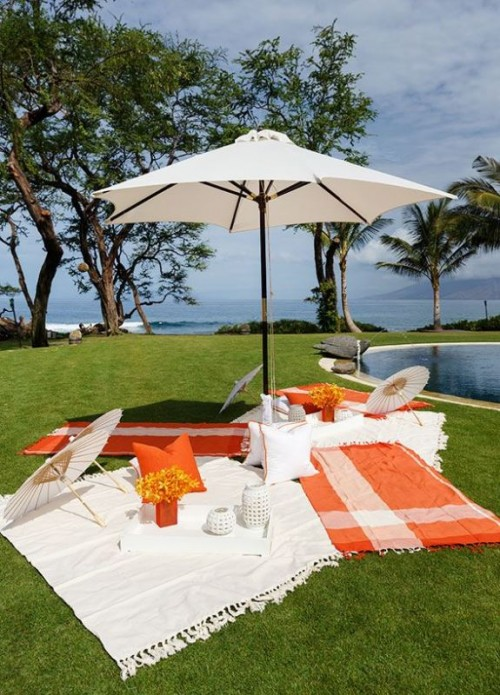 a bright picnic setting with colorful blankets, umbrellas and bright blooms by the pool