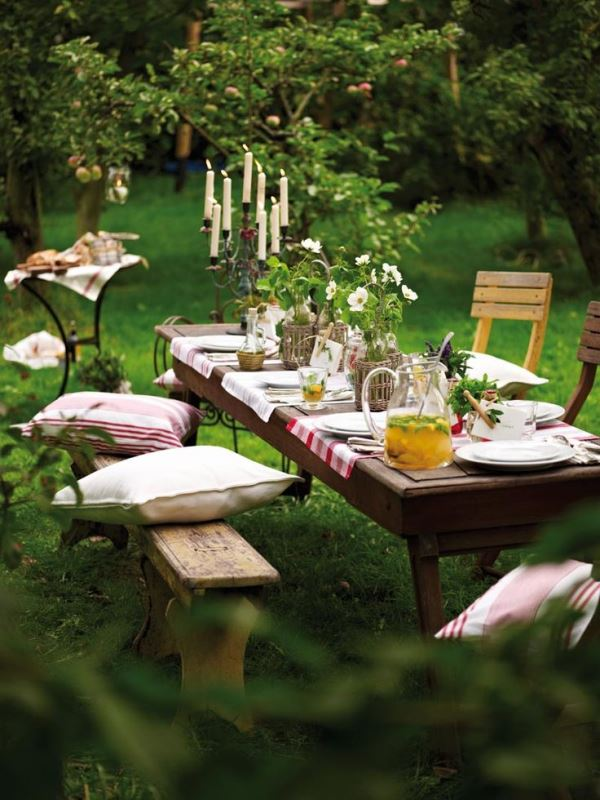 a garden picnic setting with white blooms and greenery, with candles, benches and chairs with pillows