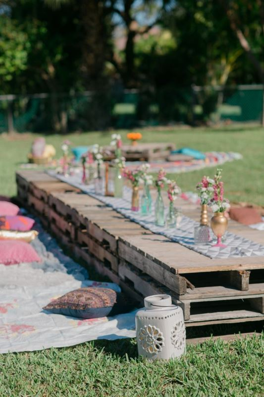 a bright boho picnic setting with a low pallet table, bright blooms, blankets and pillows for a rehearsal dinner