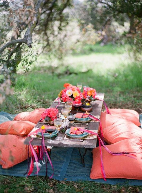 a bright boho themed rehearsal dinner picnic with bold red pillows, bold blooms, printed blankets and lots of delicious food