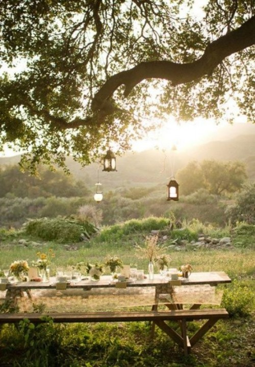 a simple summer picnic with lanterns, trestle wooden furniture, a lace tablecloth, some wildflowers