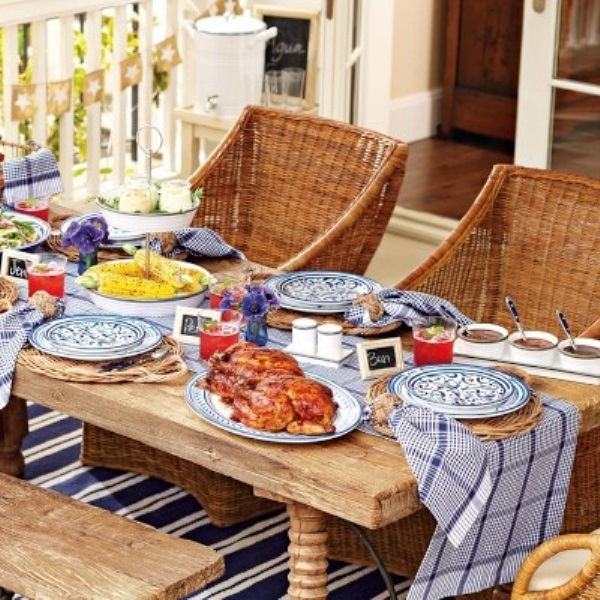 a rustic bright picnic with printed textiles, bright blooms, porcelain and wicker chairs