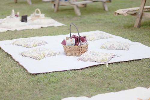 a summer picnic setting with a printed pillows, a basket with blooms is ideal for a rehearsal dinner