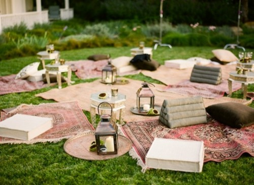 a boho summer picnic with lots of rugs, pillows, books and candle lanterns for a rehearsal dinner