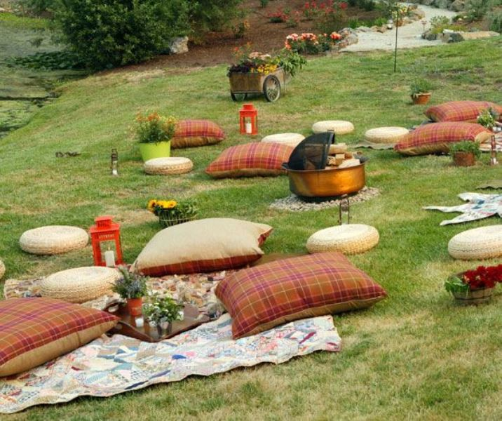 a bright and very simple picnic setting with bright and plaid pillows, blankets, candle lanterns and a fire pit