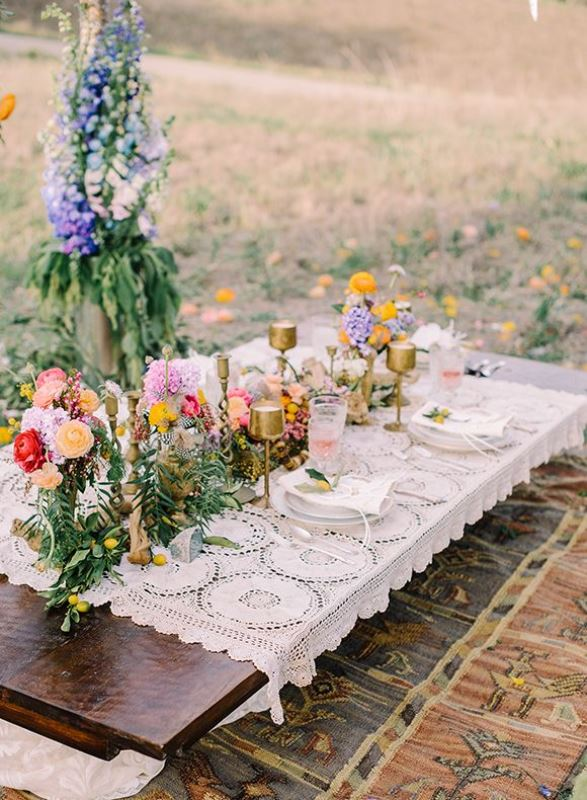 a bright summer boho picnic with a low table covered with doilies, bright blooms and greenery and gold candleholders