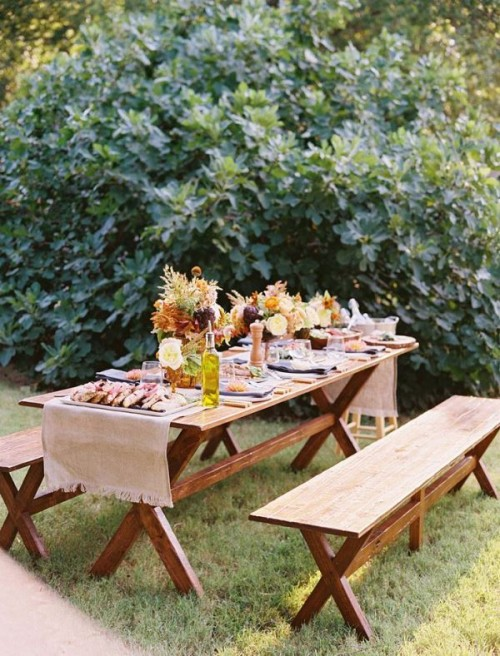 a simple picnic setting with a trestle furniture set, some bold blooms and fall leaves and delicious food