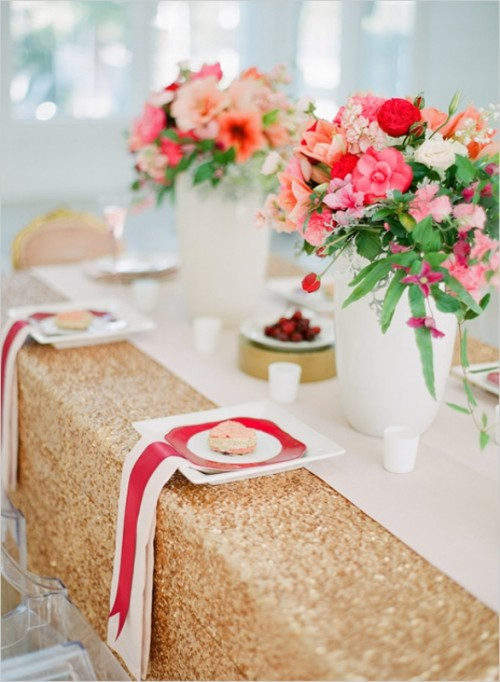 a gold sequin tablecloth, striped napkins, a printed plate and bright red and pink florals for centerpieces