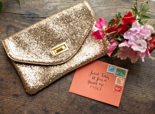 a gold sequin clutch, a coral envelope and a wedding bouquet of pink and red blooms and greenery