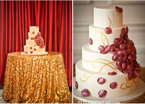 a white wedding cake decorated with burgundy petals, gold patterns served on a dessert table covered with a gold sequin tablecloth