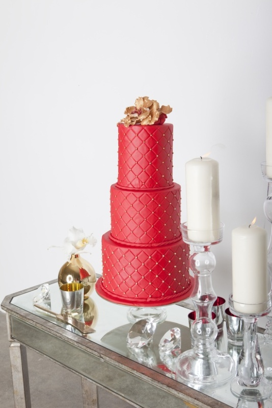 a red patterned wedding cake with gold beads and a large gold sugar flower on top