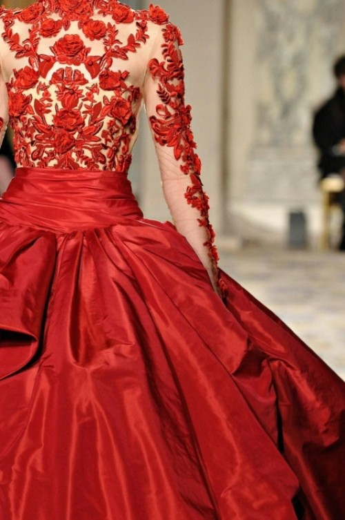 a formal A-line wedding dress with a nude and red applique bodice and a full layered skirt plus illusion sleeves