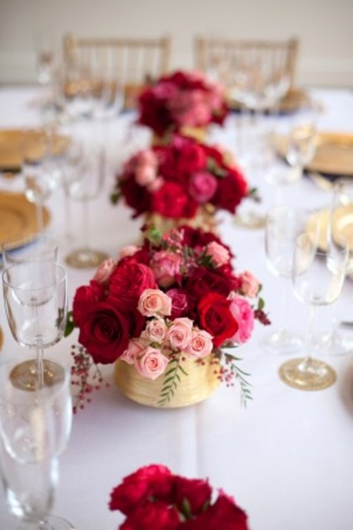 red and pink floral centerpieces with berries in gold vases are amazing to add color to your tables