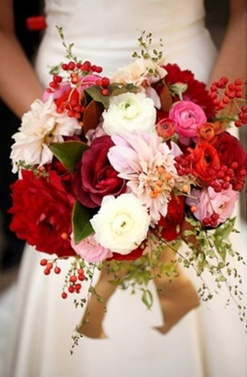 a bold wedding bouquet in deep red, pink, white, blush and with gold ribbons