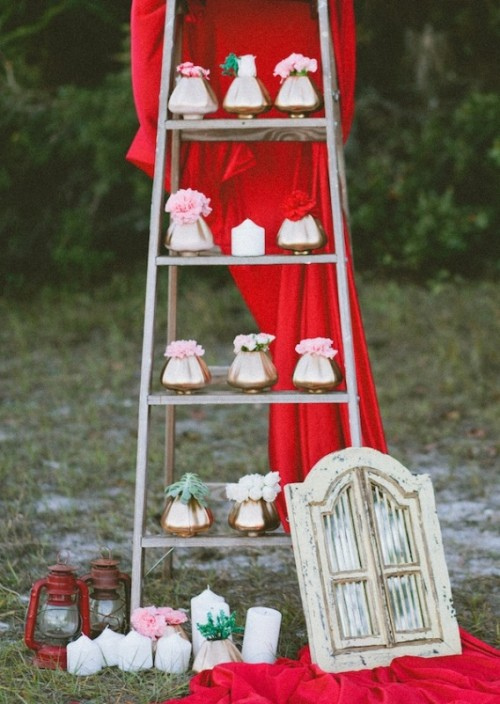 a ladder with gold vases and pink and red blooms plus some red fabric for glam and bold wedding decor