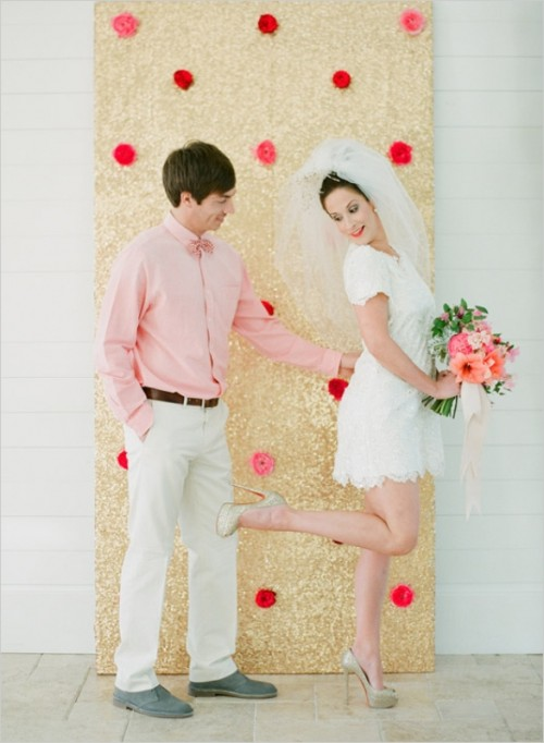 a gold sequin backdrop with pink and red blooms is great for a wedding with a color scheme and can be DIYed