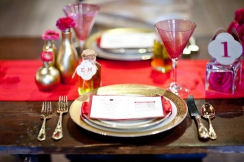 a red table runner, red glasses, gold vases with pink blooms, gold cutlery and a pink rose in a bottle