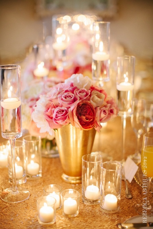 a gold vase with pink roses and candles in glass candleholders for a glam wedding table setting