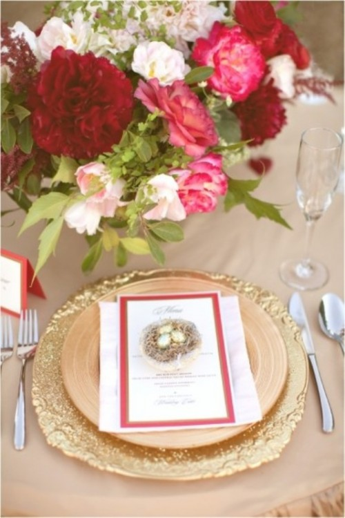 a wedding centerpiece of burgundy, pink and blush blooms and gold plates and placemats for a glam and chic look