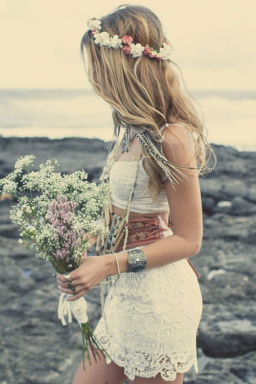 a boho chic bridal outfit with a lace crop top and a pencil skirt plus a wide sash, feather and chain earrings and a floral crown