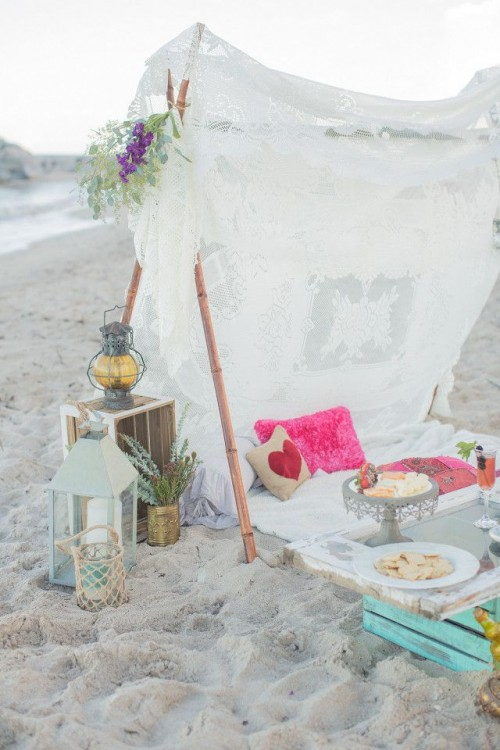 a boho beach teepee done with boho lace, colorful pillows, candle lanterns, blooms and greenery