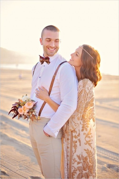 a simple boho beach groom's outfit with tan pants, a white shirt, suspenders and a printed bow tie