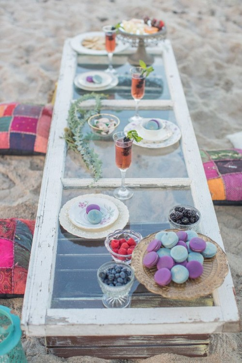 a boho beach picnic setting with a vintage window as a tabletop, colorful pillows, macarons and berries