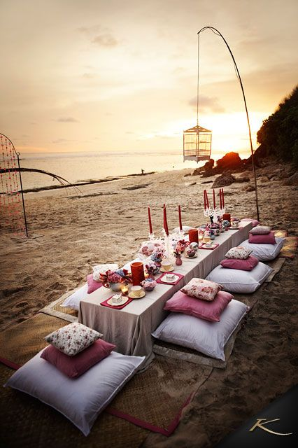a boho beach picnic setting with  with a low table, boho rugs and colorful pillows, lanterns and colorful candles