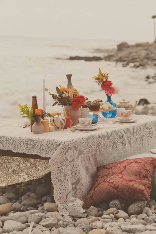 a boho beach wedding picnic setting with a low table, a lace tablecloth, colorful blooms and greenery plus pillows