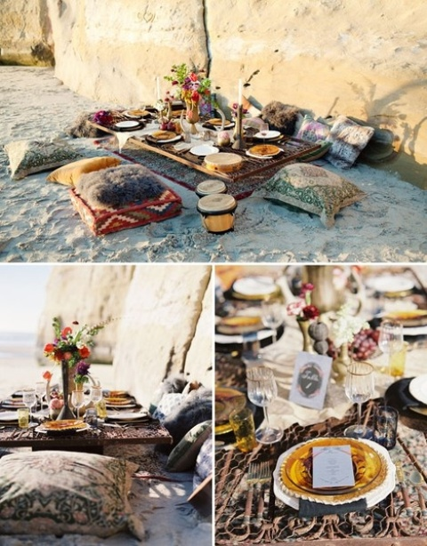 a boho beach wedding picnic with a low picnic table, boho pillows, colorful glasses and plates plus colorful blooms