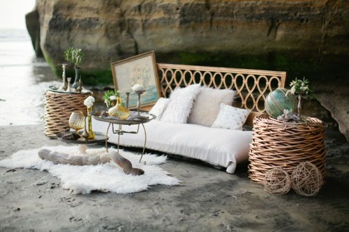 a boho beach lounge with a rattan sofa and side tables, faux fur, blooms and artworks
