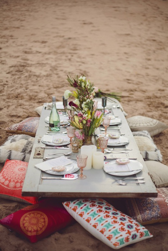 a boho beach wedding reception with a low picnic table, colorful pillows and glasses, bright blooms and greenery