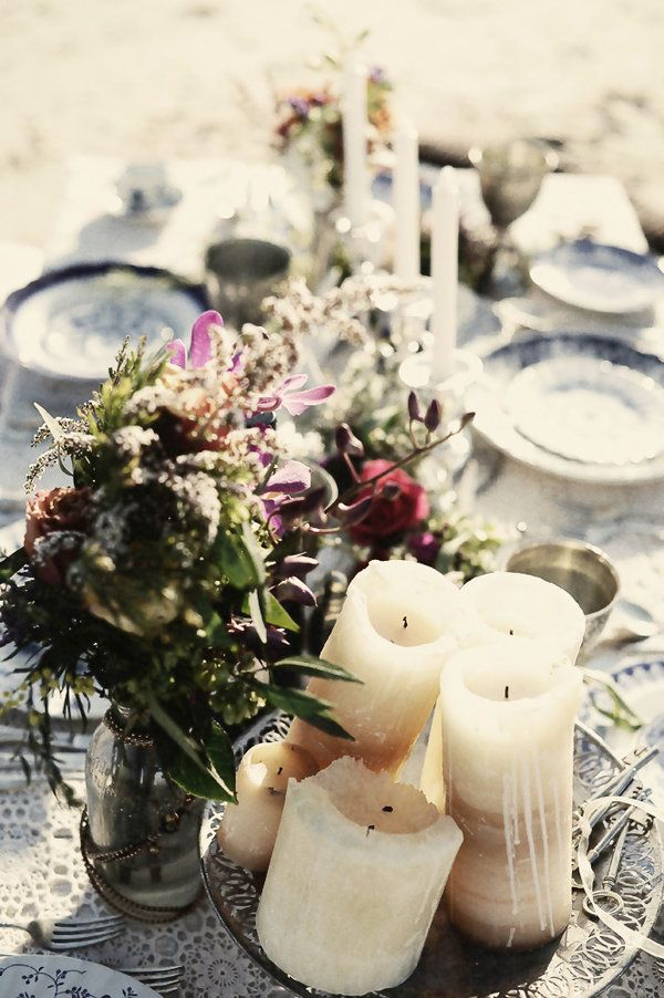 a relaxed boho beach wedding reception table with bright blooms, candles and printed plates and a tablecloth