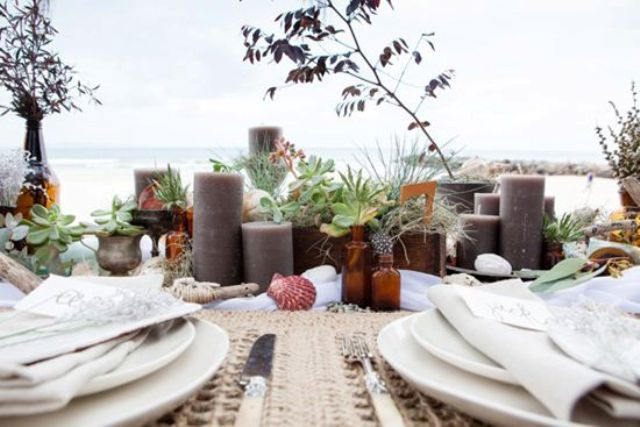 a simple boho beach reception table with wicker placemats, taupe candles, succulents and neutral porcelain