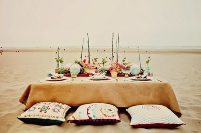 a bright boho beach place setting with an ocher tablecloth, floats, bright blooms and pillows