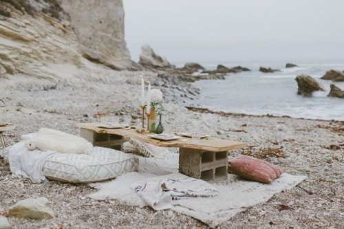 a simple boho beach reception with blankets and pillows, a concrete and wood table and candles