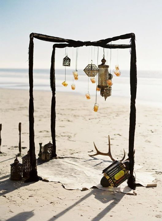 a boho beach wedding ceremony arch done with dark fabric, lanterns and candle lanterns hanging down plus a boho rug