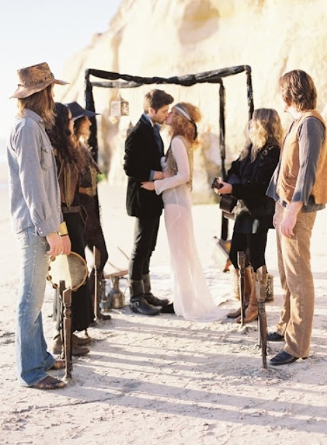 a boho beach wedding arch done in dark colors, with lanterns and some wood sticks tucked into sand