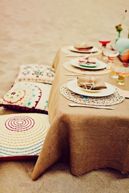 a bright boho beach setting with an ocher tablecloth, colorful pillows and plates and bright glasses