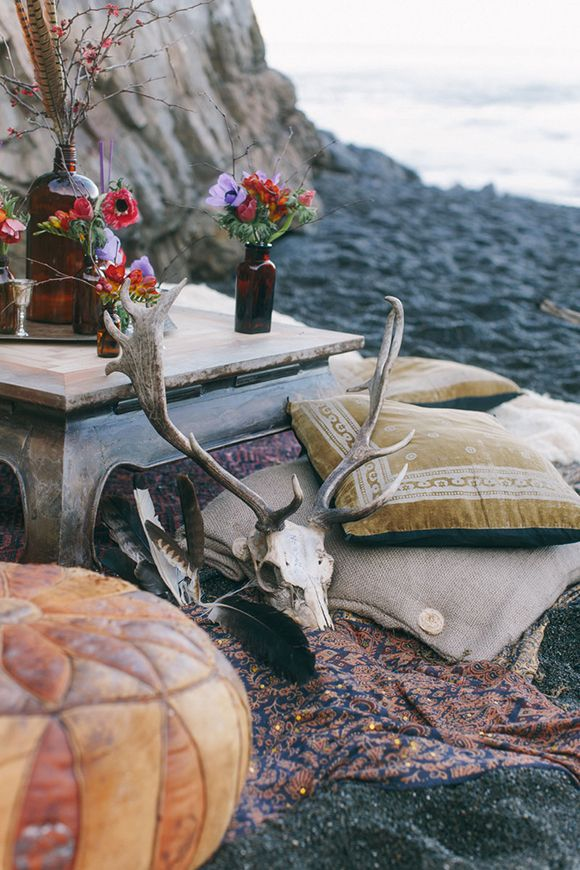 a moody boho beach setting with a low table, pillows, a leather pouf, bright blooms and a skull