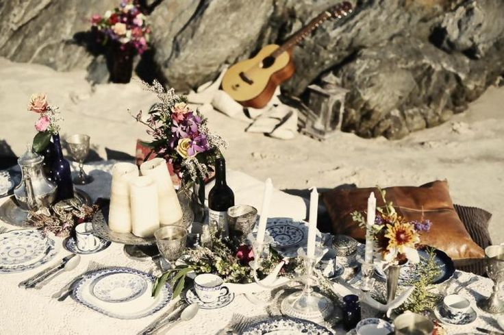 a boho beach table setting with printed plates, candles, bright blooms and various pillows