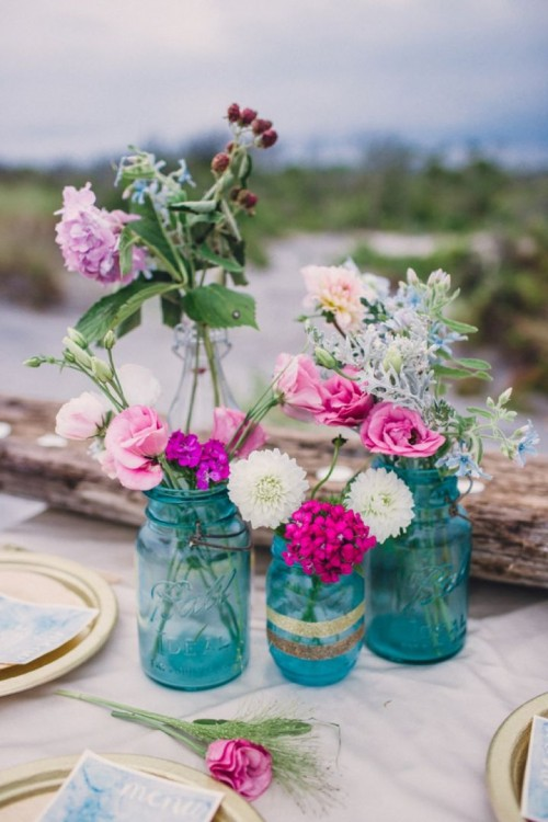 a bright boho beach wedding centerpiece with blue jars and bright blooms and driftwood with candles