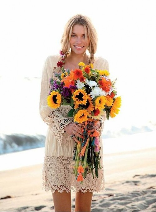 a simple and neutral boho beach wedding dress with a lace trim on the skirt and sleeves plus a bright bouquet