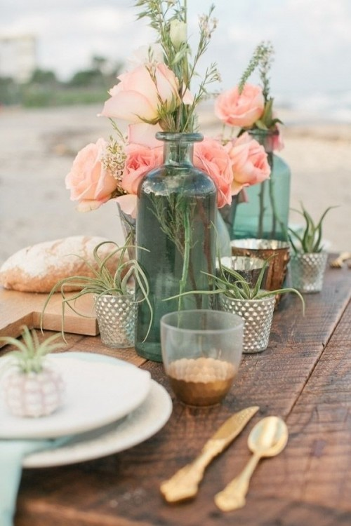 a boho beach wedding centerpiece with candle lanterns, air plants in holders, coral pink blooms and greenery in turquoise bottles
